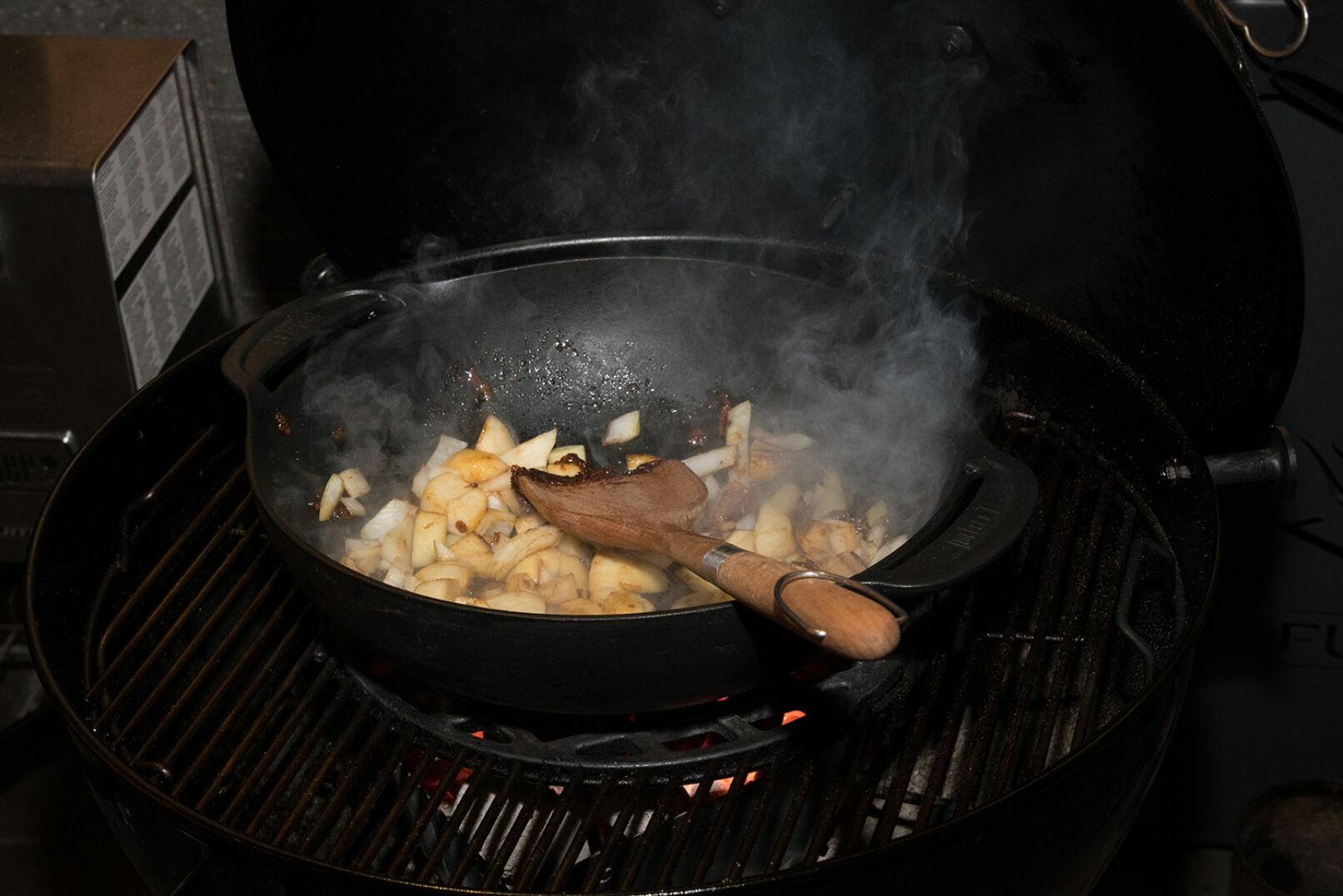 Der Wok ist nun erhitzt, der Zucker darin karamellisiert, die Birnen werden darin angeschwitzt, der Zwiebel ergänzt. - © Martin Grasberger