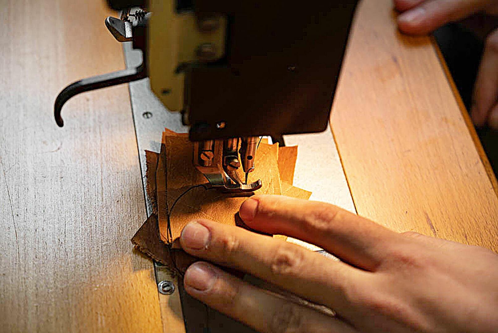 Der Taschner demonstriert, dass die Pfaff-Nähmaschine auch mit mehreren Lagen Leder zurechtkommt. - © Barbara Marko