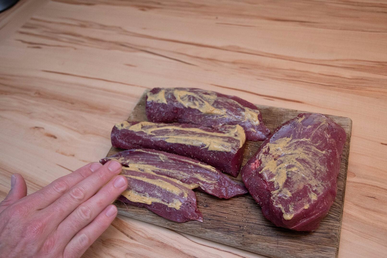 Das Fleisch mit Salz und Pfeffer würzen und mit Senf einreiben. - © Barbara Marko